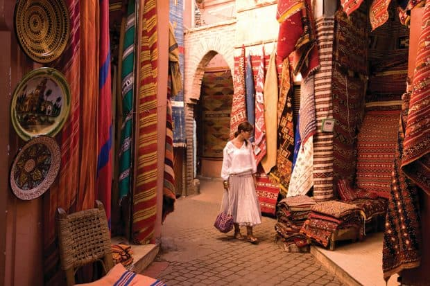 Woman looking at rugs in a Marrakech souk