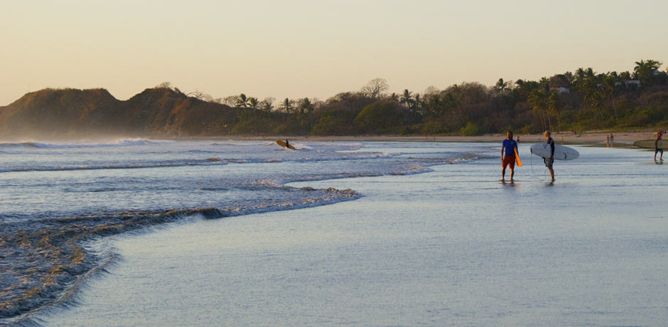 Surfers check out the early morning waves on Playa Guiones, Nosara.