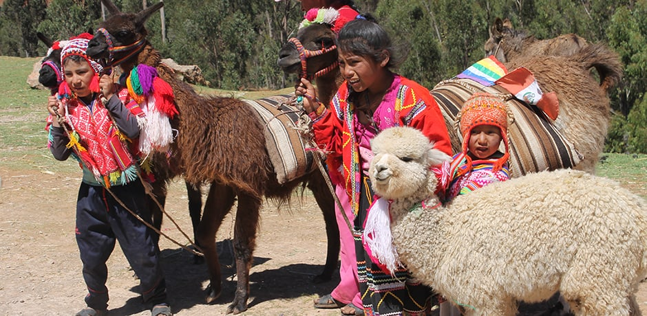 Peruvian children and their alpacas posing for a photo in the Sacred Valley