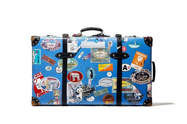 Blue suitcase covered with travel decals