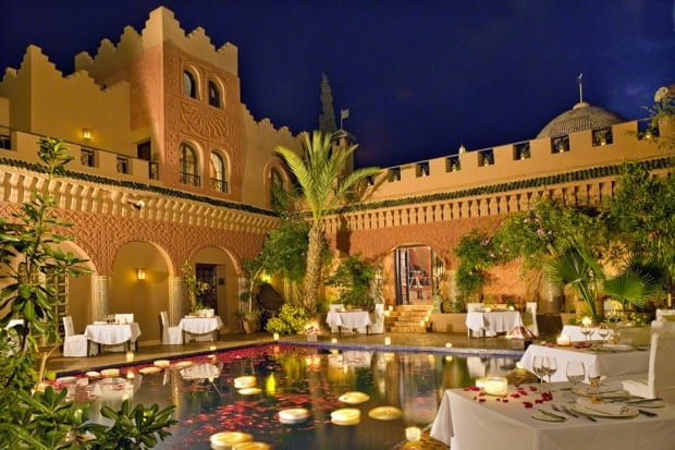 Courtyard with pool and dining tables at night at Kasbah Tamadot, Morocco