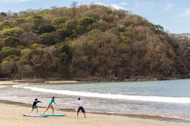 Three people practicing surfing on beach near Four Seasons Costa Rica