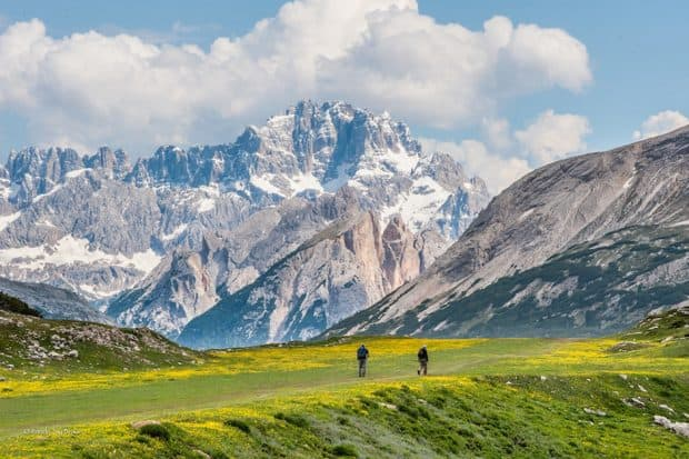 Hiking in the Dolomites with snow-capped mountains in the background