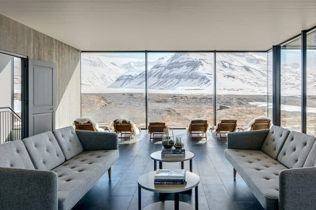 Minimalist lounge with 2 couches and snowy mountain view at Deplar Farm, Iceland