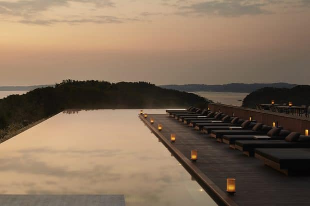 The swimming pool at dusk with lounge chairs at Amanemu