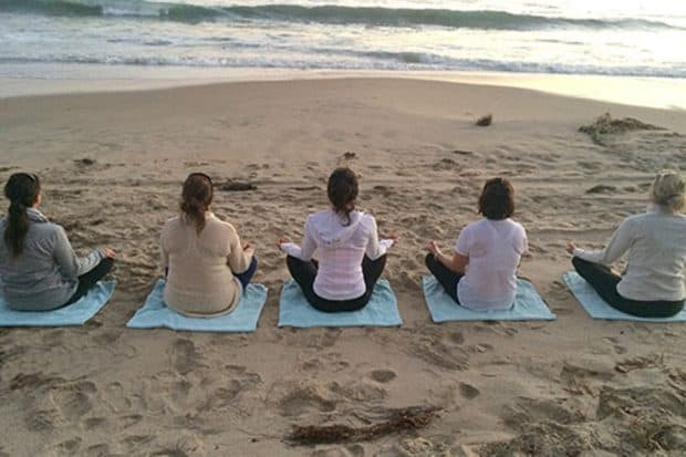 Five women meditating on a beach at The Pearl resort in California