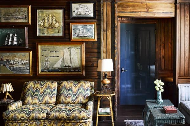 Couch with sailboat paintings on wall above at Greydon House in Nantucket