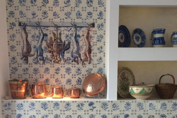 Copper dishes and blue and white tile wall in kitchen in Andalusia, Southern Spain