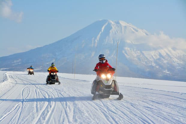 Snowmobiling in Niseko with Mount Yotei in the background. Photo by Niseko United
