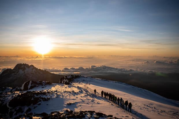 Summiting Mount Kilimanjaro at sunrise, with views over the clouds