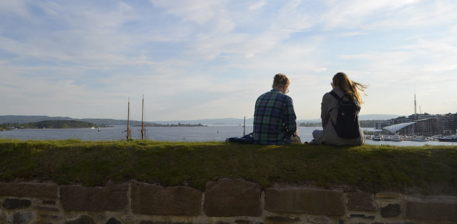 Locals enjoy the early evening light from atop the ramparts at Akershus Fortress.