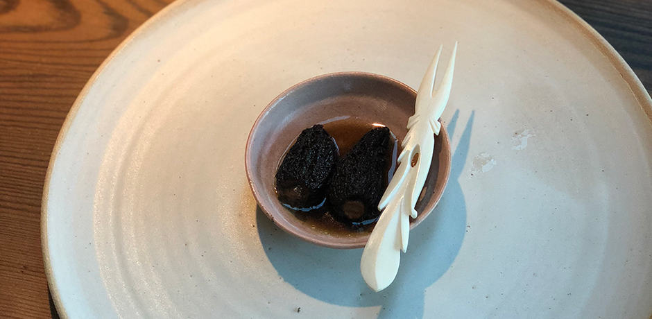 Seventh course: Preserved morels from spring. Morels served in broth with a bone utensil.