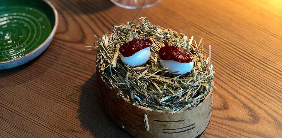 Sixth course: Quail's egg and hip berry chorizo. Boiled quail's egg topped with rose hip chorizo and served on a nest. Pop each egg for one flavorful burst.