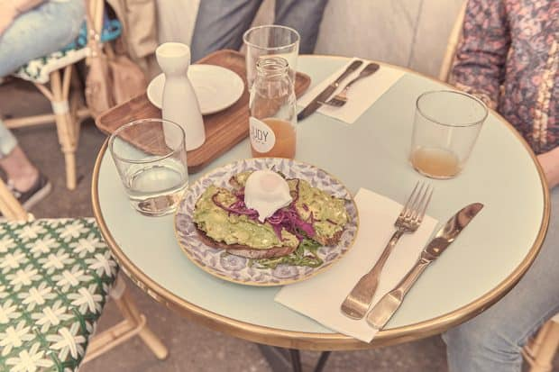 Plate of avocado toast on cafe table at Judy, the Good Life restaurant in Paris