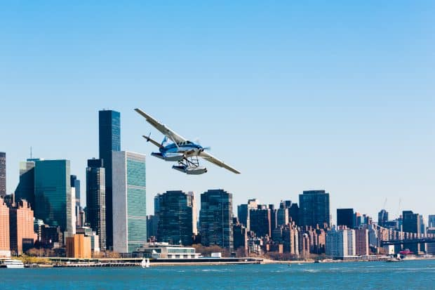 Seaplane in air over river next to New York City
