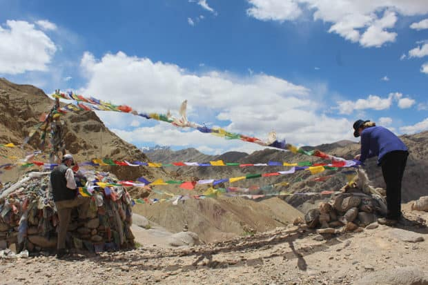 Tying prayer flags in the Himalayas while trekking with Shakti