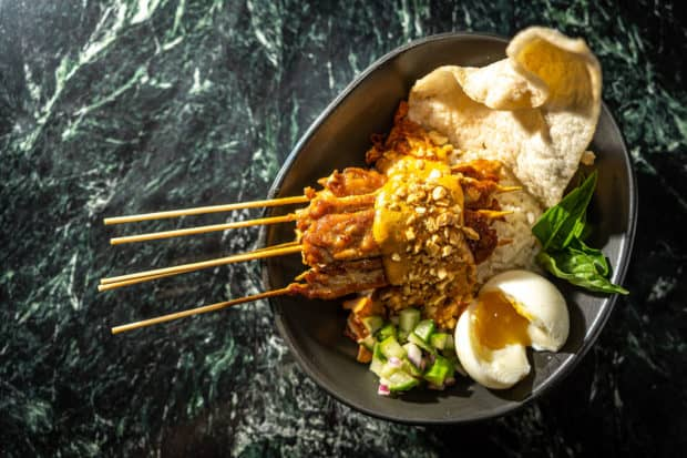 Chicken satay skewers with puffed rice and a poached egg for breakfast at Cedric and Ochi Vongeritchen's first solo venture, Wayan, in Manhattan. Photo by Noah Fecks.