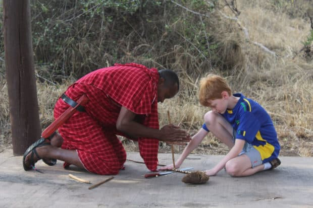 Eliza's son learning how to make a traditional Maasai fire.