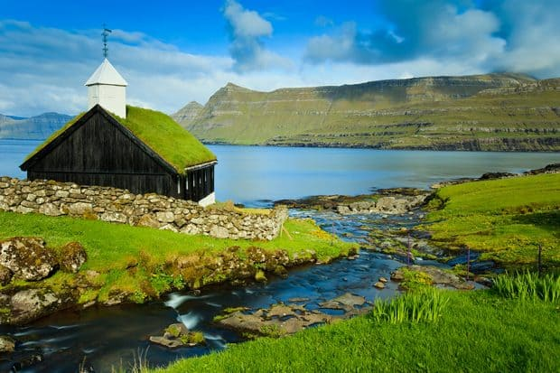 A stream running into the Funningsfjordur and a traditional turf or grass roofed church, located in the picturesque village of Funningur.
